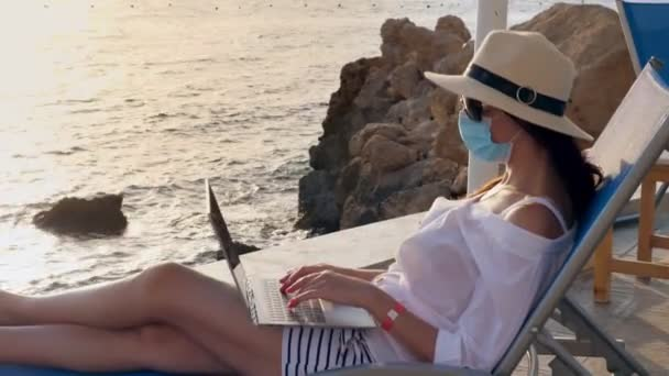 young woman in protective mask, sun hat and summer clothes, working on laptop, sitting on sun lounger by the sea. work remotely. new normal. Life after Covid19.