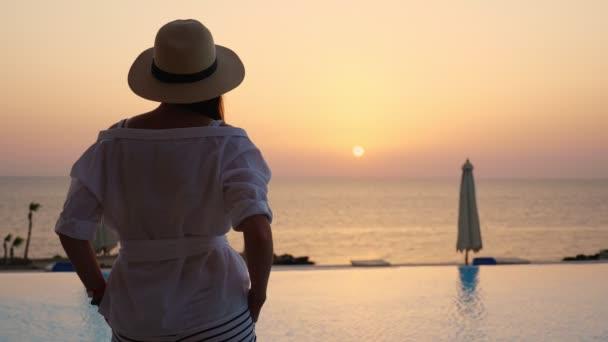 pohled zezadu na mladou ženu v letních šatech a slunečním klobouku, jak stojí u bazénu a užívá si východu slunce. Léto. přímořské letovisko. cestovní a rekreační koncept