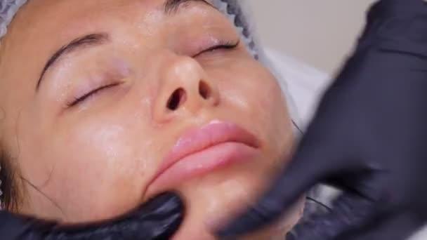 zblízka, kosmetolog, v černých lékařských rukavicích, provádí proceduru péče o pleť, masáž obličeje u ženy, pomocí speciálního kosmetického gelu, v kosmetické klinice nebo kosmetickém salonu.