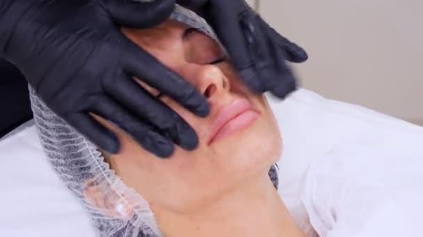 közeli, fekete orvosi kesztyűs kozmetikus kozmetikai krémet alkalmaz a masszázsos női arcra. kozmetikai klinika vagy szépségszalon bőrápolási eljárása.