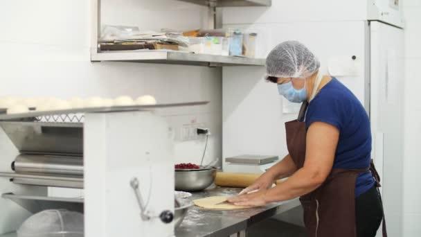 Kochen. Backwaren. Köchin, in Schutzhandschuhen und Maske, schneidet rohen Teig auf dem Küchentisch in Stücke, bestreut mit Mehl. gesunde Ernährung. Wiedereröffnung der Kantine. Freiwilligenarbeit und Wohltätigkeit