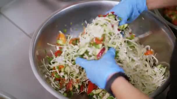 Kochen. Nahaufnahme. In Schutzhandschuhen bereitet der Koch einen Salat in einer großen Schüssel zu. gesunde Ernährung. Sicherheitskonzept. Wiedereröffnung der Kantine. Freiwilligenarbeit und Wohltätigkeit
