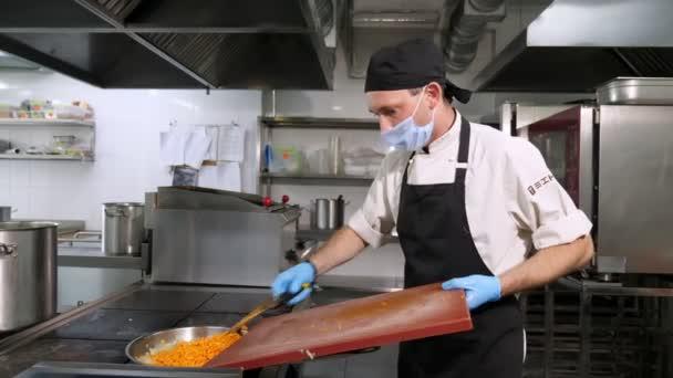 Kochen. Nahaufnahme. Der Koch, in Schutzmaske und Handschuhen, rührt die Zwiebeln und Karotten in der Pfanne. gesunde Ernährung. Ehrenamtliche Arbeit. Wiedereröffnung der Kantine. Sicherheitskonzept.