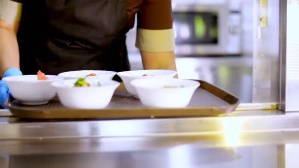 Kochen. Nahaufnahme. Kellner in Schutzhandschuhen stellt Schüsseln mit Salaten in die Selbstbedienungsvitrine. Küche Cafeteria Buffet mit Essen. gesunde Ernährung. Freiwilligenarbeit und Wohltätigkeit. Wiedereröffnung
