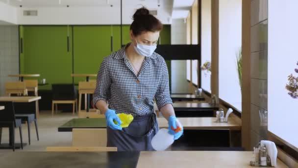 Kellnerin mit Schutzhandschuhen und Maske desinfiziert Tische für Besucher mit antiseptischem Spray zum Schutz vor Coronavirus. Wiedereröffnung von Cafeteria oder Restaurant. Sicherheitskonzept.