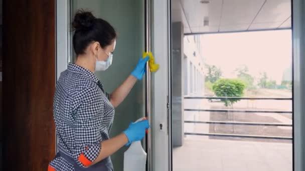 Putzfrau, mit Schutzmaske und Handschuhen, wischt Türklinken in Restaurants oder öffentlichen Einrichtungen mit Antiseptikum ab. Schutz vor Coronavirus, Sicherheitskonzept