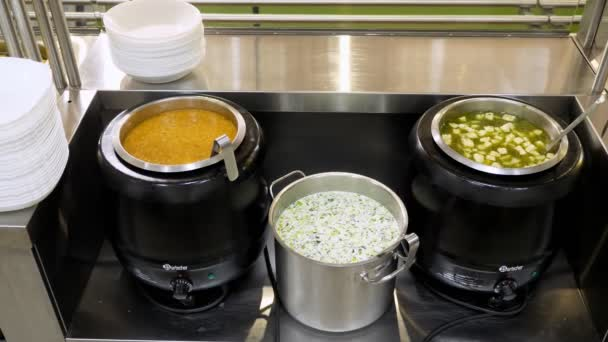 Nahaufnahme. Vitrine mit frisch zubereiteten ersten Gängen, Suppen in Terrinen, in Selbstbedienungscafeteria oder Buffetrestaurant. gesunde Ernährung. Freiwilligenarbeit und Wohltätigkeit. Wiedereröffnung. Sicherheitskonzept