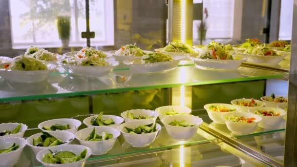 showcase s různými čerstvě připravenými zeleninovými saláty v samoobslužné jídelně nebo bufetové restauraci. zdravé jídlo. dobrovolnictví a charity. znovuotevření. koncepce bezpečnosti