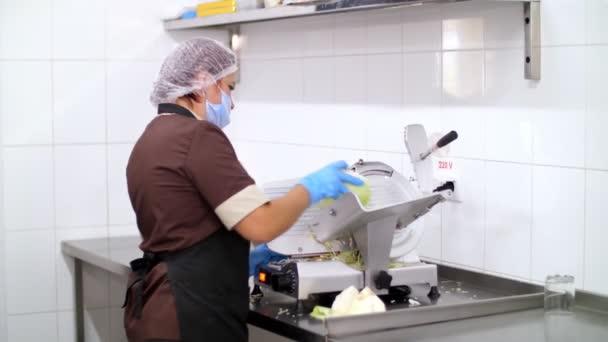 Kochen. Küchenhilfe schneidet in Schutzhandschuhen und Maske frischen Kohl auf einem Elektroschredder. gesunde Ernährung. Wiedereröffnung nach Covid-19. Sicherheitskonzept. Freiwilligenarbeit und Wohltätigkeit.