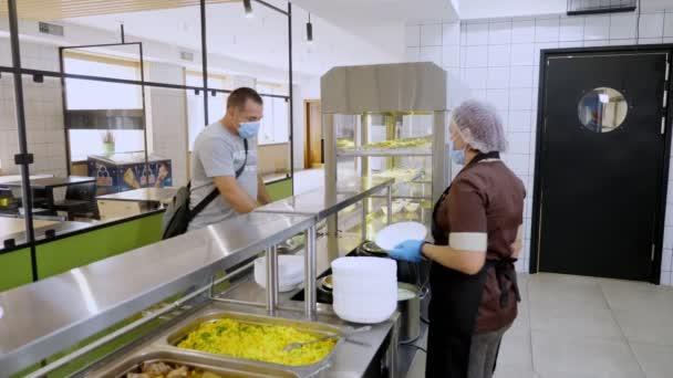 CHERKASSY, UKRAINE, 14. AUGUST 2020: Ein Mann mit Schutzmaske isst in der Selbstbedienungskantine oder im Buffetrestaurant zu Mittag. gesunde Ernährung. Wiedereröffnung. Sicherheitskonzept