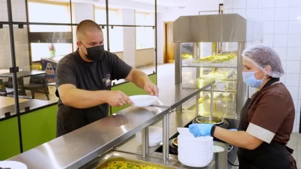 CHERKASSY, UKRAINE, AUGUST 14, 2020: egy férfi, védőmaszkban, ebédel önkiszolgáló büfében vagy büfében. Egészséges étel. Újranyitás. biztonsági koncepció