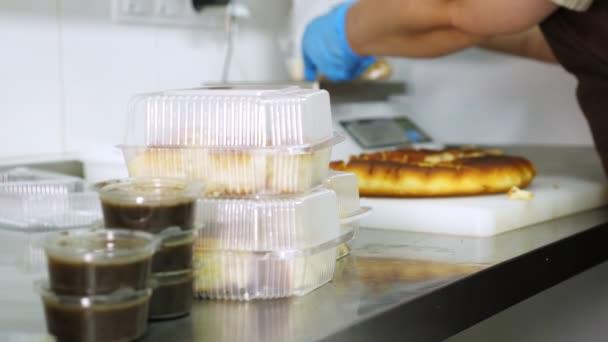 Kochen. Nahaufnahme, Volontär, Küchenhelfer, in Schutzhandschuhen, packen kostenlos geschnittenes Brot in Lunchboxen, um es armen Menschen zukommen zu lassen. Essensausgabe. Wohltätigkeitsprojekt, Hilfe spenden,