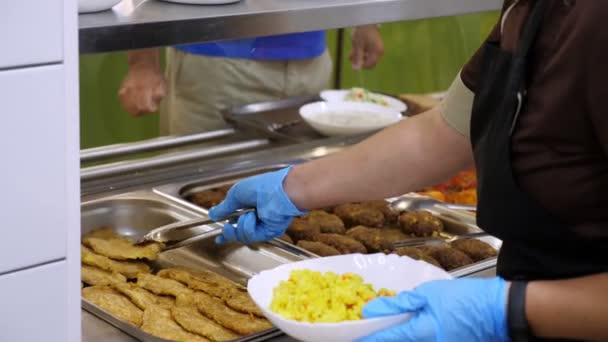vaření. detailní záběr. servírka, v ochranných rukavicích, dává jídlo na talíř pro zákazníka v samoobslužné jídelně nebo bufetové restauraci. znovu otevřít po covid-19. koncepce bezpečnosti. zdraví potravin.