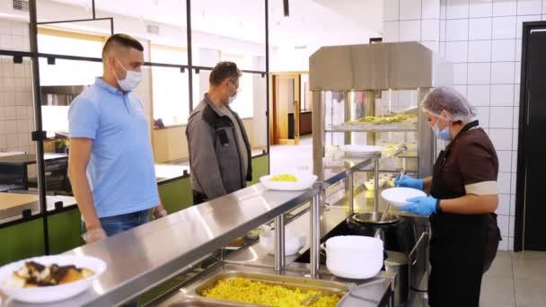 CHERKASSY, UKRAINE, 14. AUGUST 2020: Männer in Schutzmasken essen in Selbstbedienungscafés oder Buffetrestaurants zu Mittag. gesunde Ernährung. Wiedereröffnung. Sicherheitskonzept
