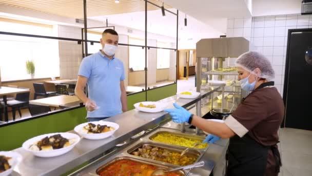CHERKASSY, UKRAINE, 14. AUGUST 2020: Ein Mann mit Schutzhandschuhen und Maske nimmt in der Selbstbedienungscafeteria oder im Buffetrestaurant das Mittagessen ein. gesunde Ernährung. Wiedereröffnung. Sicherheitskonzept