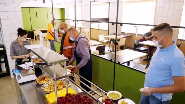 CHERKASSY, UKRAINE, 14. AUGUST 2020: Männer in Schutzmasken nehmen Mittagessen ein und bezahlen in der Selbstbedienungskantine oder im Buffetrestaurant bar. Wiedereröffnung nach Covid-19. Sicherheitskonzept. gesunde Ernährung