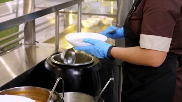 Nahaufnahme. Kellnerin in Schutzhandschuhen gießt Suppe in Teller für Kunden in Selbstbedienungs-Cafeteria oder Buffet-Restaurant. Wiedereröffnung nach Covid-19. Sicherheitskonzept. gesunde Ernährung.