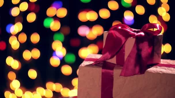 krásně zabalené dárky s růžovými stuhami. prezentuje na bokeh světla nebo zářící girlandy pozadí. detailní záběr, rotace. Vánoce nebo Nový rok. charitativní koncept. slavnostní atmosféra.