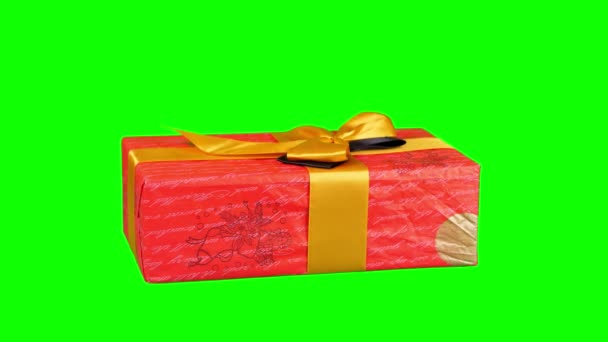 gyönyörűen becsomagolt ajándék, jelen elszigetelt zöld háttérrel. Közelkép, rotáció. Karácsony vagy újév. ünnepi csomagolás, ajándékdoboz.