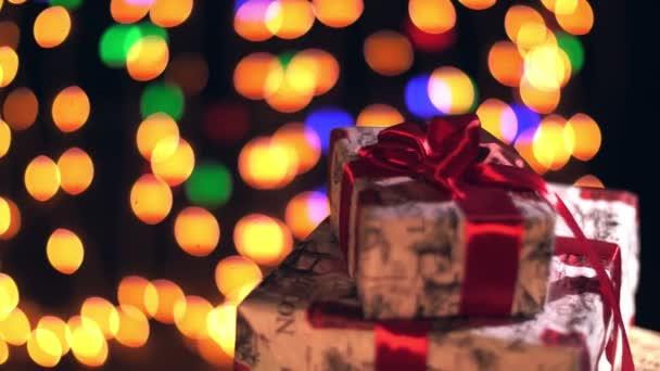 krásně zabalené dárky s červenými stuhami. prezentuje na bokeh světla nebo zářící girlandy pozadí. detailní záběr, rotace. Vánoce nebo Nový rok. charitativní koncept. slavnostní atmosféra.