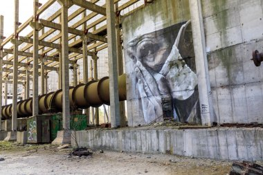 Eastern Europe, Ukraine, Pripyat, Chernobyl. April 10, 2018. Inside the unfinished cooling tower, a mural depicts a tired doctor. Painted by Australian artist Guido van Helton in 2016 based on a photograph by Igor Kostin.