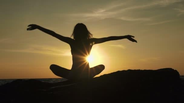 Sziluettjét meditáció lány lótusz helyzet a háttérben lenyűgöző tengeri kő.