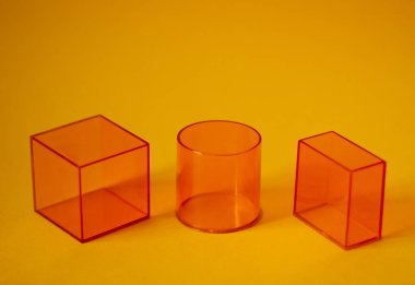 3d geometric transparent orange shapes - parallelepipid, cylinder and cube. The concept of simplicity in geometry. Educational manual for students.