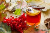 Viburnum és forró tea naranccsal, ánizzsal és fahéjjal őszi levelekkel az asztalon.