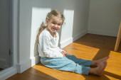 Édes kislány egy világos szobában, minimális tárgyak a szobában, a gyermek örül, ül a padlón a napfényben.
