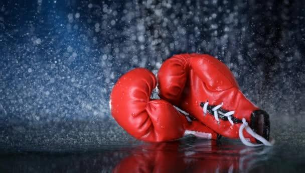Červené boxerské rukavice na vodní kapky pozadí. Sportovní životní styl. Motivace. Dosažení cíle. Chraň se. Pohybová fotografie