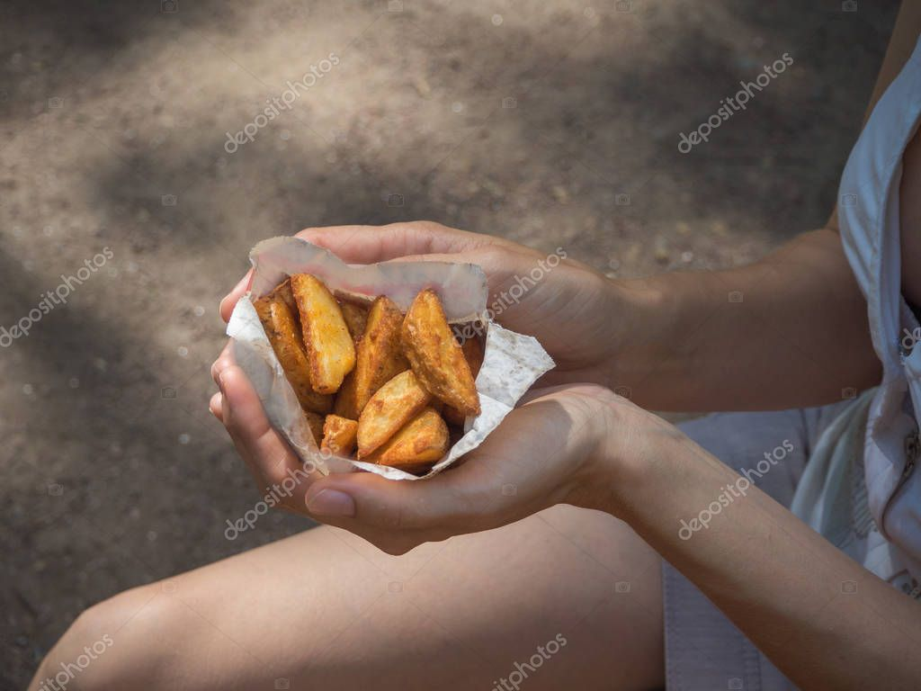 A girl holding a pack of fries in hand in the street. Small pack of potato fries, fast snack