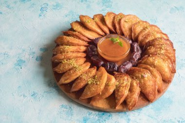 Arabic sweets. Arabian Qatayef pancake stuffed with sweet cheese and nuts on the blue table