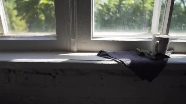 Na okenní římse se vychlazená káva, za oknem se zelené větve stromů ovíjejí větrem