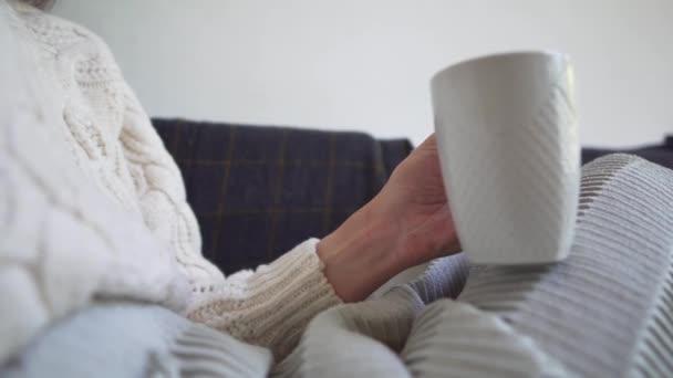 Közeli kéz-lány tart egy csésze friss kávé, bujkál egy takaró, ül egy hangulatos kanapén egy hideg őszi nap