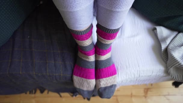 Female legs in brown-pink warm knitted socks close-up on a cozy sofa with a blanket. Life philosophy of Lagom, the ability to enjoy minimalism and simple things
