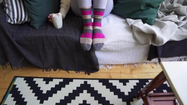 Legs of a girl on a sofa in warm multi-colored socks on a cold winter day in a Scandinavian interior. Hygge philosophy, the joy of home comfort