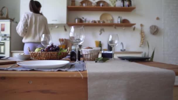 Krásná dřevěná kuchyně-dívka připravuje příchod hostů, připravuje produkty k večeři. Kuchyňský stůl se šatkou, Žena na pozadí