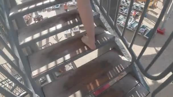 Woman climbs stairs in a water park, legs close-up, slow motion