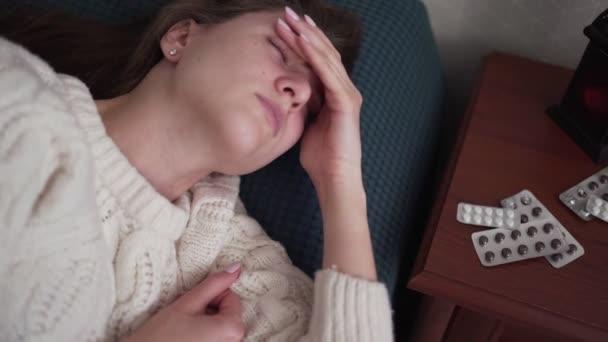 eine kranke Frau mit Fieber und Kopfschmerzen liegt im Bett und betrachtet die Verpackung von Tabletten und Medikamenten. starke Migräne und Schmerzmittel, Mädchen im Schlafzimmer