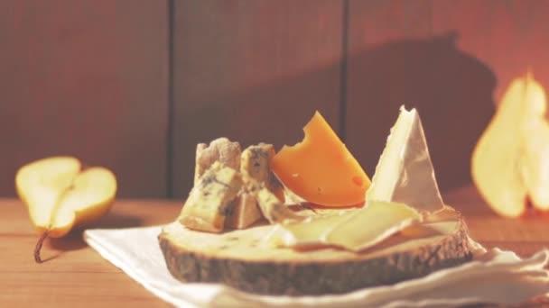 Různé typy sýrů a kouskem hrušky na dřevěných deskách. Niva, camembert a tvrdý sýr na dřevěný podstavec. Výběr sýrů a zralé hrušky