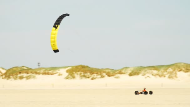 Kite buggying - vehicle powered by a traction kite racing through a sandy coast