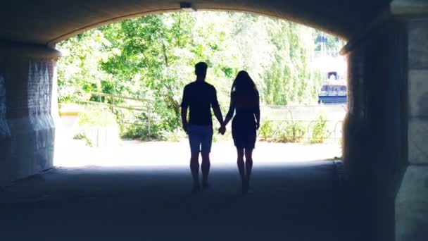 Silhouette of a couple going through the tunnel, hugging and kissing