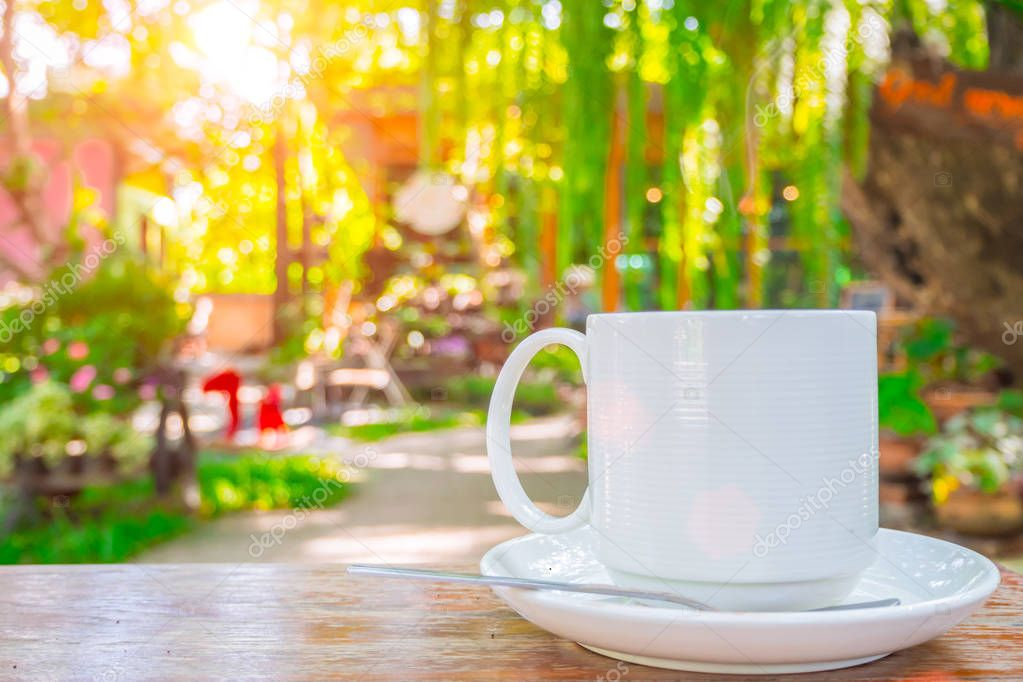 coffee cup on wooden table green outdoor nature garden background.