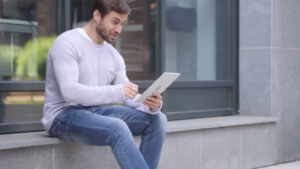 Vzrušený muž slaví úspěch na notebooku sedí na schodech