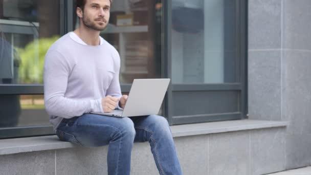 Zamyšlený pohledný muž myšlení při práci na notebooku sedí u okna