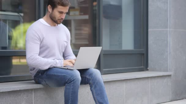 Handsome Man Typing on Laptop while Sitting Outside Office