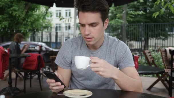 Man Drinking Coffee and using Smartphone while Sitting in Cafe Terrace
