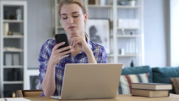 Frau nutzt Smartphone, surft online bei der Arbeit