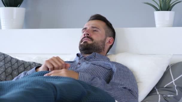 Snažil se zívání muž ležící v posteli