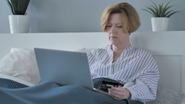 Online nakupování na notebooku staré starší žena v posteli, platba